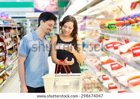 couple buys meat at the supermarket - stock photo