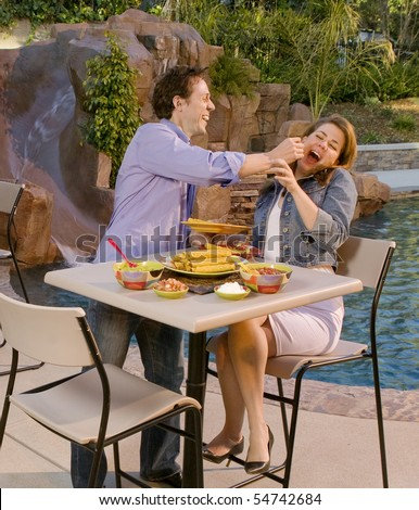 Couple by pool side with Mexican food - stock photo