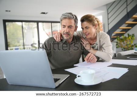 Couple calculating financial savings on internet - stock photo