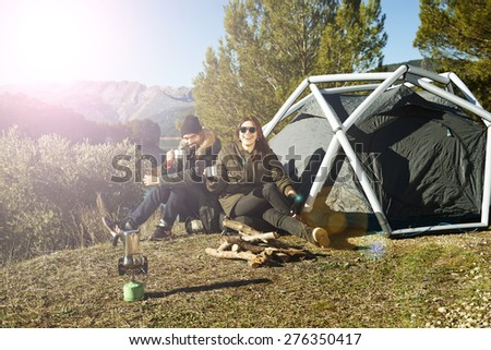 Couple camping drinking coffee near tent smiling happy outdoors in mountain forest enjoying sun looking at camera. Happy multiracial couple relaxing. Asian woman, Caucasian man.  - stock photo