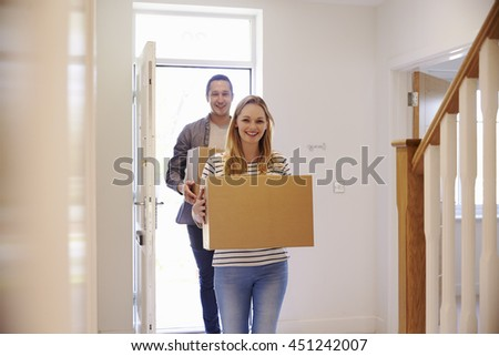 Couple Carrying Boxes Into New Home On Moving Day - stock photo