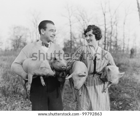 Couple carrying pigs - stock photo
