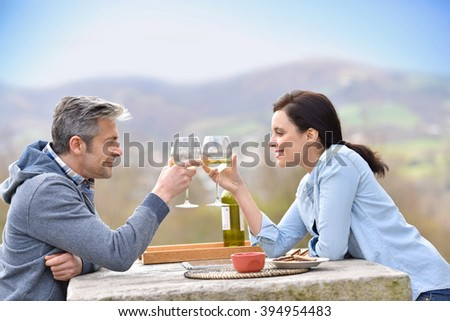 Couple cheering with wine sitting in courtyard - stock photo
