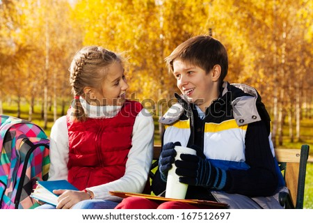 Couple children, boy and girl sitting on the bench in autumn park talking to each other after school holding books and coffee mug - stock photo