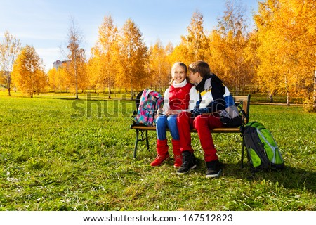 Couple children, boy whispering to girl sitting on the bench in autumn park with backpacks laying near by - stock photo