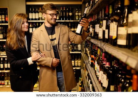 Couple choosing alcohol in a liquor store  - stock photo