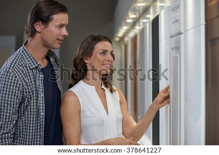 Couple choosing cabinets in a modern kitchen shop showroom while planning their dream kitchen - stock photo