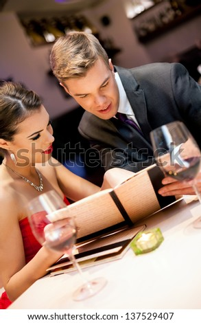 Couple choosing meal from the menu card in restaurant - stock photo