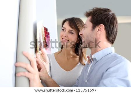 Couple choosing paperwall colour for their new home - stock photo
