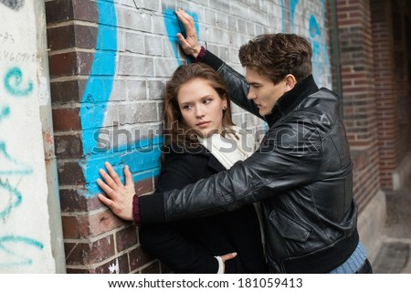 Couple conflict on street, aggressive man hold young sad woman leaning on wall, violence sex crime, negative urban city street life, relationship problem - stock photo