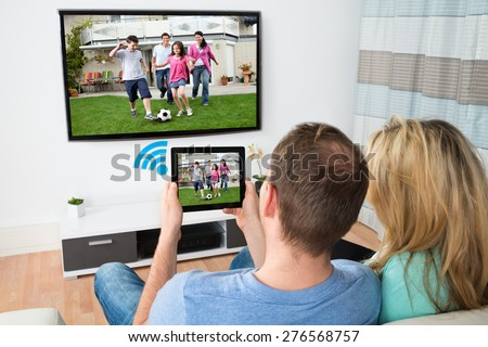Couple Connecting Television And Digital Table Through Wifi Signal At Home - stock photo