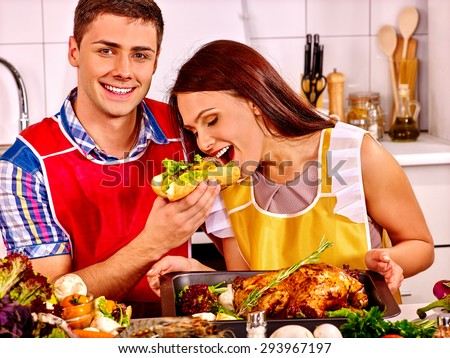 Couple cooking chicken and eating hot dog at kitchen.Woman is feeding man - stock photo