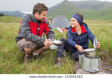 Couple cooking outside on camping trip and smiling in the countryside - stock photo