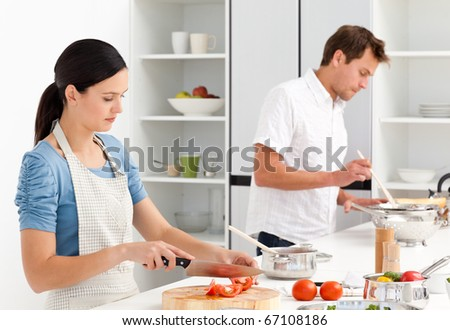 Couple cooking together their lunch in the kitchen - stock photo