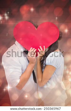 Couple covering their kiss with a heart against light design shimmering on red - stock photo