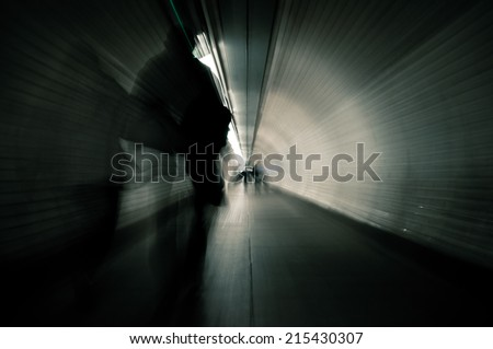 Couple crossing a dark tunnel. Image with blur zoom effect - stock photo