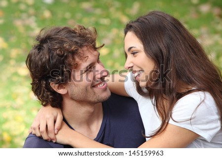 Couple cuddling and flirting in a park with a green unfocused background            - stock photo