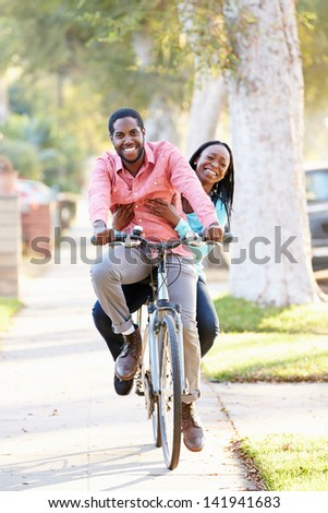 Couple Cycling Along Suburban Street Together - stock photo