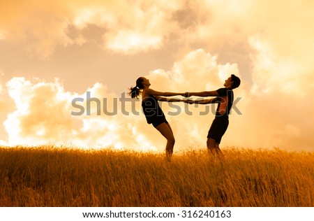 Couple dancing in a field of tall grass.  - stock photo