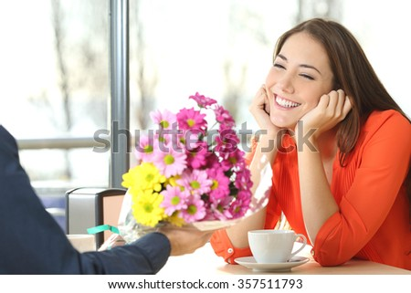 Couple dating and boyfriend giving a bouquet of flowers to his candid girlfriend in a coffee shop - stock photo