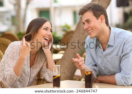 Couple dating and flirting while taking a conversation and looking each other in a restaurant - stock photo