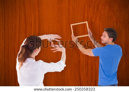 Couple deciding to hang picture against wooden oak table - stock photo