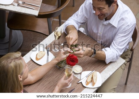 Couple dining in restaurant, man giving woman red rose, elevated view - stock photo