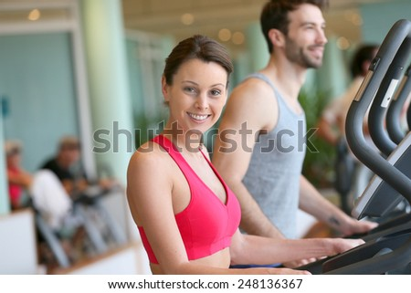 Couple doing cardio training program in fitness center - stock photo