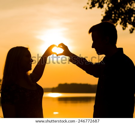 Couple doing heart shape with their hands on lake shore. People silhouettes vintage photo. - stock photo