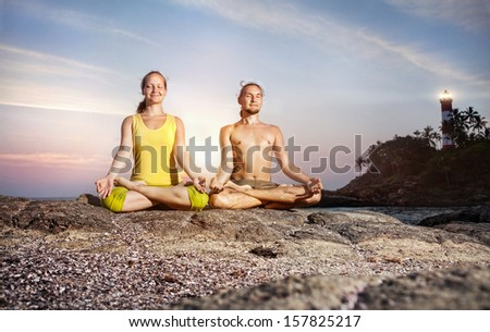 Couple doing meditation in lotus pose on the stone near the sea at lighthouse background in Kovalam, Kerala, India - stock photo
