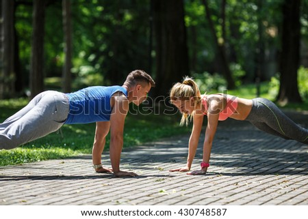 Couple doing push-ups at the park.Workout outdoors. - stock photo