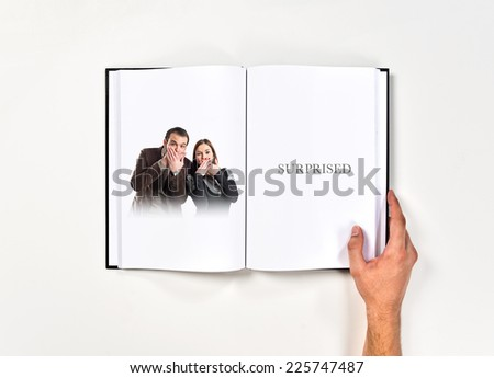 Couple doing surprise gesture printed on book - stock photo