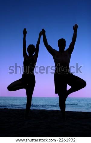 Couple doing yoga exercise on the beach - stock photo