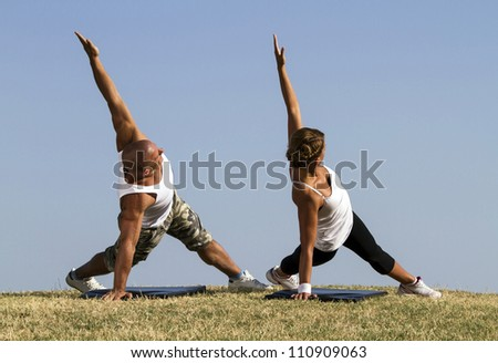 Couple doing yoga in nature. Beautiful blue skies in bacground. - stock photo
