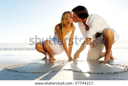 Couple draw a heart in the sand and share a romantic kiss on the beach in summer - stock photo
