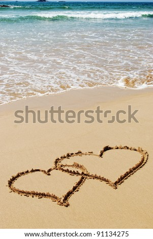 couple drawing a heart on wet golden beach sand - stock photo