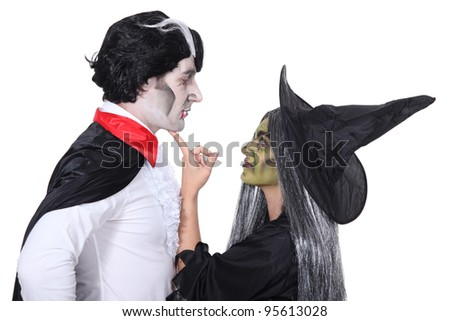 Couple dressed as witch and vampire - stock photo