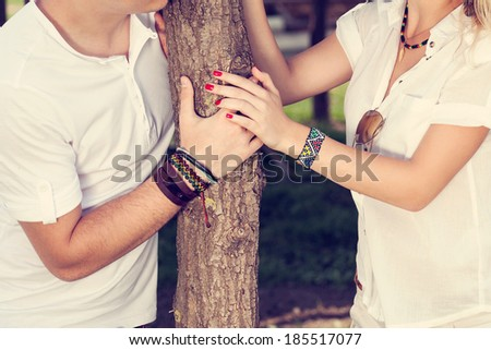 Couple dressed in white, holding hands - stock photo