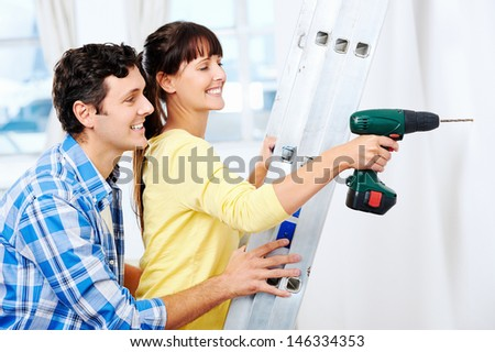 couple drilling in wall doing diy at new home after moving in together - stock photo