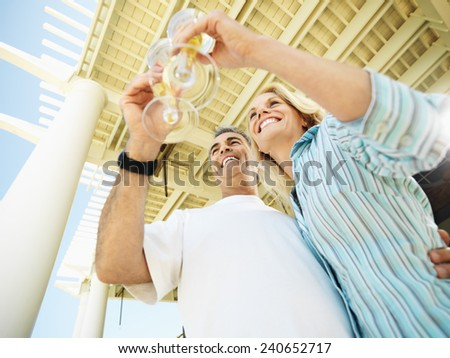 Couple Drinking Champagne at Resort - stock photo