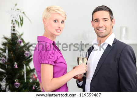 Couple drinking champagne in front of a christmas tree - stock photo