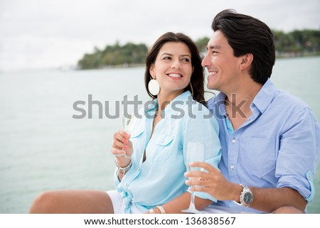 Couple drinking champagne outdoors enjoying their summer holidays - stock photo
