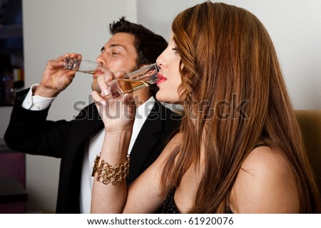 Couple drinking liquor shots in restaurant or nightclub - stock photo