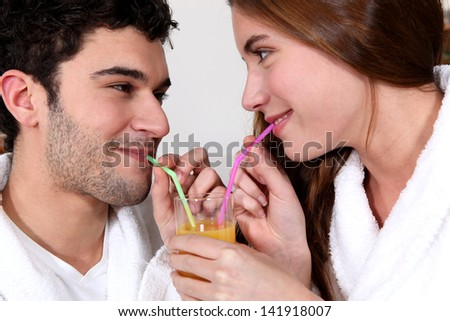 couple drinking orange juice from the same glass with straws - stock photo