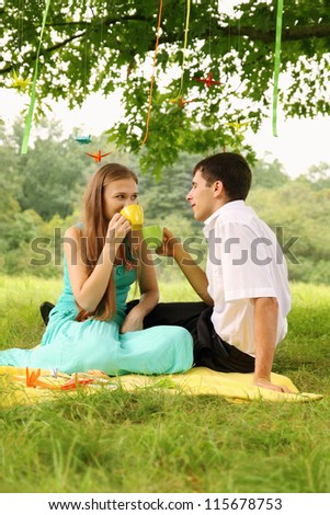 Couple drinking tea under a tree with paper cranes - stock photo