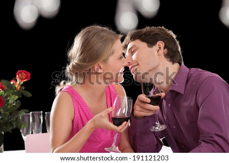 Couple drinking wine and kissing during romantic dinner - stock photo