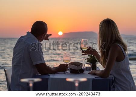 Couple drinking wine at beach restaurant  on sunset - stock photo