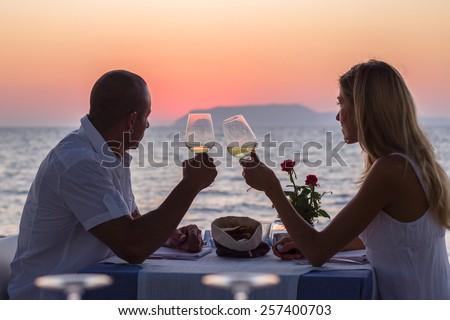 Couple drinking wine in sea restaurant at sunset - stock photo