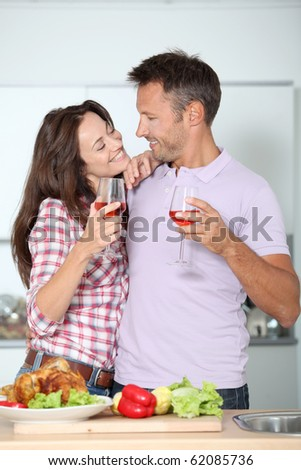 Couple drinking wine while fixing dinner - stock photo
