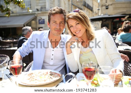 Couple eating lunch at outdoor restaurant - stock photo